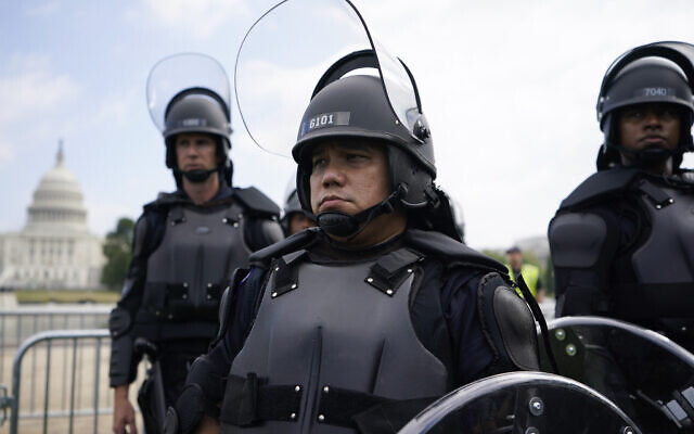 Police in riot gear patrol as people attend a rally near the US Capitol in Washington, Saturday, September 18, 2021. (AP/Brynn Anderson)
