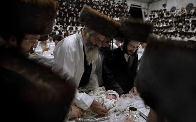 """Yaakov Tabersky, right, presented his firstborn son, Yossef on a silver platter to Jewish priests from the Lelov Hassidic dynasty, during the """"Pidyon Haben"""" ceremony in Beit Shemesh, Israel, on Thursday, September 16, 2021. The Pidyon Haben, or redemption of the firstborn son, is a Jewish ceremony hearkening back to the biblical exodus from Egypt. (AP Photo/Oded Balilty)"""