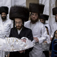 """Yaakov Tabersky, carries his 30-day-old son Yossef, the great grandchild of the chief rabbi of the Lelov Hassidic dynasty, during the """"Pidyon Haben"""" ceremony in Beit Shemesh, Israel, on September 16, 2021. (AP/Oded Balilty)"""