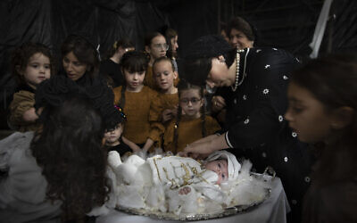 """Ultra-Orthodox Jewish women adorn 30-day-old Yossef Tabersky, the great grandchild of the chief rabbi of the Lelov Hassidic dynasty, during the """"Pidyon Haben"""" ceremony in Beit Shemesh, Israel, on September 16, 2021. (AP/Oded Balilty)"""