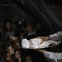 """Ultra-Orthodox Jews are holding 30-day-old Yossef Tabersky, the great grandchild of the chief rabbi of the Lelov Hassidic dynasty, during the """"Pidyon Haben"""" ceremony in Beit Shemesh, Israel, on September 16, 2021. (AP Photo/Oded Balilty)"""