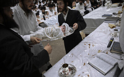 """Yaakov Tabersky, right, presented his firstborn son, Yossef on a silver platter to Jewish priests from the Lelov Hassidic dynasty, during the """"Pidyon Haben"""" ceremony in Beit Shemesh, Israel, on September 16, 2021. (AP/Oded Balilty)"""