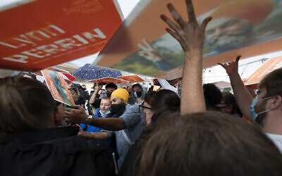 New Democratic Party supporters use signs as rain shields, as NDP Leader Jagmeet Singh greets people during a campaign stop in Pitt Meadows, British Columbia, on Sunday, September 19, 2021. (Jonathan Hayward/The Canadian Press via AP)