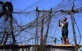 Muqtada Haider turns the switches to transfer electricity to private homes in Baghdad, Iraq, on Friday, September 10, 2021. (AP Photo/Hadi Mizban)