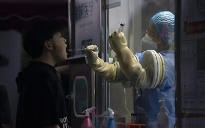 A man gets swapped during a nuclei test for COVID-19 in Beijing Sept. 18, 2021 (AP Photo/Ng Han Guan)