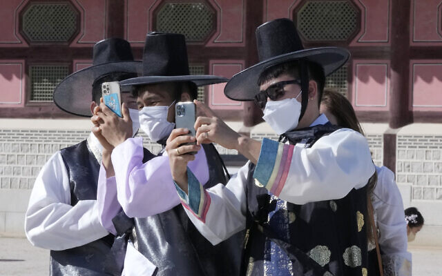 Men wearing face masks as a precaution against the coronavirus take photos as they visit to celebrate Chuseok holidays, the Korean version of Thanksgiving Day, at the Gyeongbok Palace in Seoul, South Korea, on September 22, 2021. (AP Photo/Ahn Young-joon)