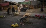An Afghan boy sits on a wheelbarrow as he waits for customers at a street fruit and vegetable market in Kabul, Afghanistan, September 22, 2021. (AP Photo/Bernat Armangue)