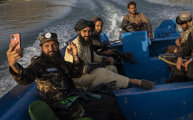 Taliban fighters take a selfie while enjoying a boat ride in the Qargha dam, outskirt of Kabul, Afghanistan, September 24, 2021. (AP Photo/Bernat Armangue)
