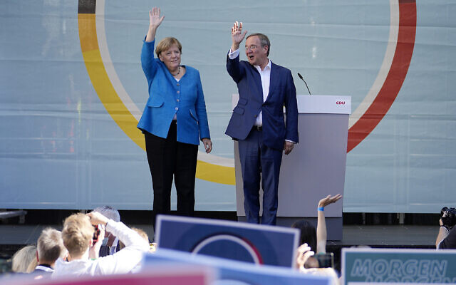 Chancellor Angela Merkel and Governor Armin Laschet, top candidate for the upcoming election, wave to supporters at the final election campaign event of the Christian Democratic Party, CDU, ahead of the German general election in Aachen, Germany, on September 25, 2021. (AP Photo/Martin Meissner)