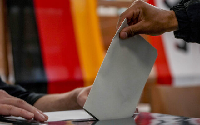 A man casts his ballot for the German elections in a polling station in Berlin, Germany, September 26, 2021. (AP Photo/ Michael Probst)