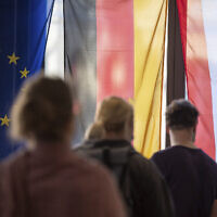Voters stand in front of a European, German and Berlin flag at a polling station to cast their votes in Berlin, Germany, Sunday,  Sept. 26, 2021. German elect a new national parliament. (Sebastian Gollnow/dpa via AP)