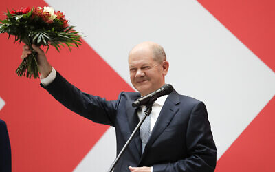 Olaf Scholz, top candidate for chancellor of the Social Democratic Party (SPD), holds a bunch of flowers after a press statement at the party's headquarter in Berlin, Germany, Monday, Sept. 27, 2021.  (AP Photo/Lisa Leunter)