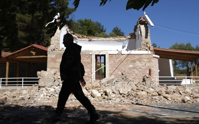 A resident passes next to a damaged Greek Orthodox chapel after a strong earthquake in Arcalochori village on the southern island of Crete, Greece, on September. 27, 2021. (AP Photo/Harry Nikos)