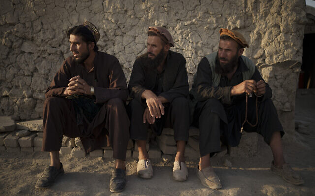 Afghans sit outside a mosque in a poor neighborhood where hundreds of internally displaced people from the eastern part of the country have been living for years, in Kabul, Afghanistan, September 27, 2021. (AP Photo/Felipe Dana)