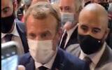 This image from video made available by Lyonmag.com shows an egg thrown toward French President Emmanuel Macron, left, to hit him on the shoulder as he walks through the restaurant trade fair in Lyon, France, September 27, 2021. (LYONMAG.COM via AP)