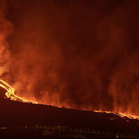 Lava flows from a volcano on the Canary island of La Palma, Spain in the early hours of Tuesday Sept. 28, 2021. A Spanish island volcano that has buried more than 500 buildings and displaced over 6,000 people since last week lessened its activity on Monday, although scientists warned that it was too early to declare the eruption phase finished and authorities ordered residents to stay indoors to avoid the unhealthy fumes from lava meeting sea waters. (AP Photo/Saul Santos)