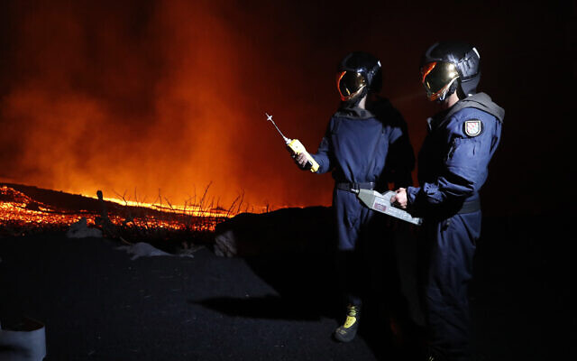 In this photo made available by Ume (Unidad Militar de Emergencias), Military Emergency Unit personal take gas reading measurements near a volcano on the Canary island of La Palma, Spain, in the early hours of Sept. 28, 2021 (Luismi Ortiz/UME via AP)