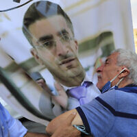 The father of Ibrahim Harb (center), a Lebanese man who was critically injured in the massive explosion at Beirut's port last year and who died on Monday nearly 14 months after the blast, mourns on his son's portrait during his funeral procession, in Beirut, Lebanon, on Tuesday, September 28, 2021. (AP Photo/Hussein Malla)