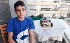 Barak Houry, 12, sits next to a small-scale model of a fire-fighting robot concept he built on his own. Houry was killed while riding his bike on Yom Kippur on September 15, 2021. (Courtesy of the Houry family)