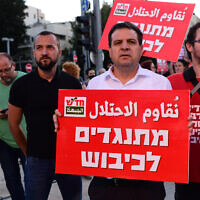 Leader of the Joint List Ayman Odeh is seen carrying a sign which reads 'Against the Occupation' during a protest in Tel Aviv, on May 15, 2021. (Tomer Neuberg/Flash90)