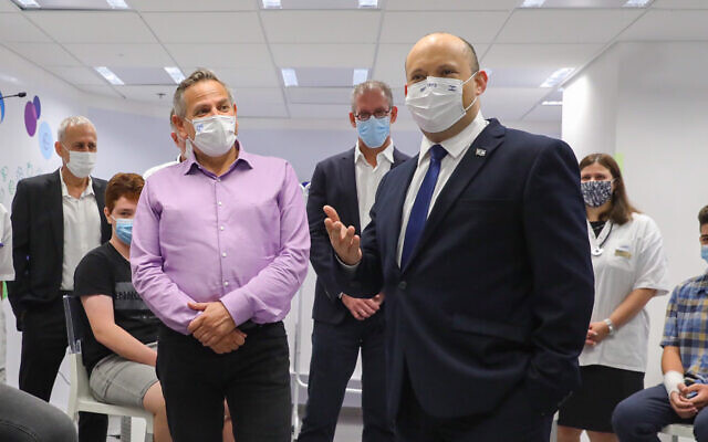 Prime Minister Prime Minister Naftali Bennet (right) and Health Minister Nitzan Horowitz attend a press conference at a Maccabi vaccination center in Holon, on June 29 2021. (Marc Israel Sellem/Pool/Flash90)