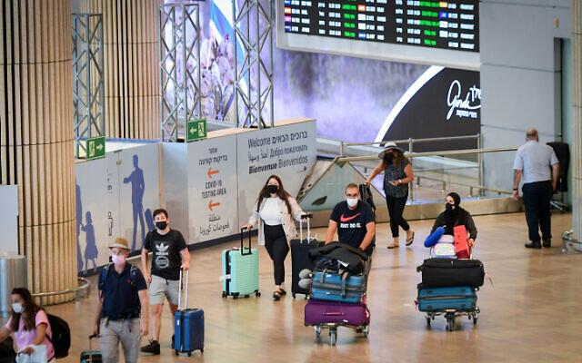 Illustrative image: travellers wear protective face masks at Ben Gurion International Airport. (Avshalom Sassoni/FLASH90)