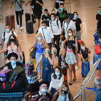 Travelers wear protective face masks inside Ben Gurion International Airport on August 5, 2021. (Avshalom Sassoni/FLASH90)