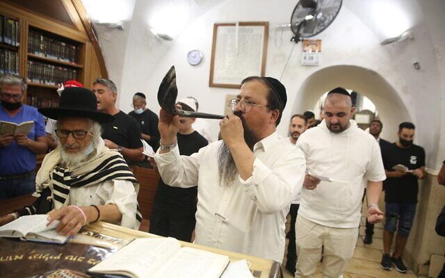 A Jewish man blows a shofar in Meron, northern Israel, on August 9, 2021, ahead of the Jewish New Year. (David Cohen/Flash90)