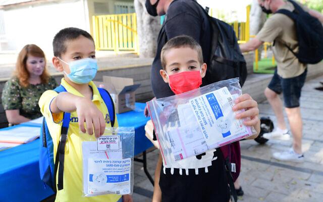 Kids at a school in Tel Aviv hold up antigen coronavirus testing kits on August 30, 2021. (Avshalom Sassoni/Flash90)