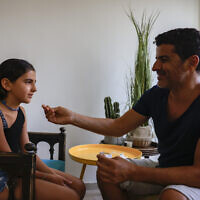 A father tests his daughter with a COVID-19 rapid antigen home kit test ahead of the first day of school, in Jerusalem on August 31, 2021. (Olivier Fitoussi/Flash90)