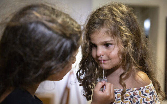 A girl tests her sister with a COVID-19 rapid antigen  home kit test ahead of the first day of school, in Jerusalem on August 31, 2021.(Olivier Fitoussi/Flash90)