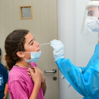 Children are tested for COVID-19 at a Clalit Medical Center in Katzrin, September 6, 2021. (Michael Giladi/Flash90)