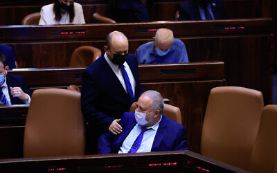 Prime Minister Naftali Bennett seen with Minister of Finance Avigdor Liberman during a vote on the first reading of the state budget in the Knesset, September 2, 2021. (Olivier Fitoussi/Flash90)