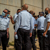 Police officers and prison guards stand at the scene of a prison escape of six Palestinian terrorists outside the Gilboa prison in northern Israel, on September 6, 2021. (Flash90)