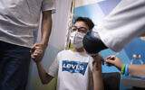 Israelis receive their dose of the COVID-19 vaccine at a Clalit health care maintenance organization, on September 09, 2021, in Jerusalem. (Olivier Fitoussi/Flash90)