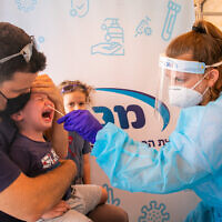 Healthcare workers take Covid-19 test samples of Israelis at a Maccabi healthcare test center in Modiin, on September 13 2021. (Yossi Aloni/Flash90)