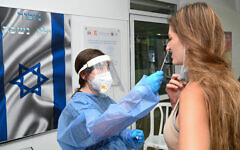 A Magen David Adom volunteer takes a swab sample from an Israeli woman at a coronavirus testing site in the Golan Heights town of Katzrin, on September 15, 2021. (Michael Giladi/Flash90)