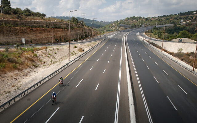 Israelis ride their bicycles along the empty Jerusalem roads on Yom Kippur, on September 16, 2021. (Jamal Awad/Flash90)
