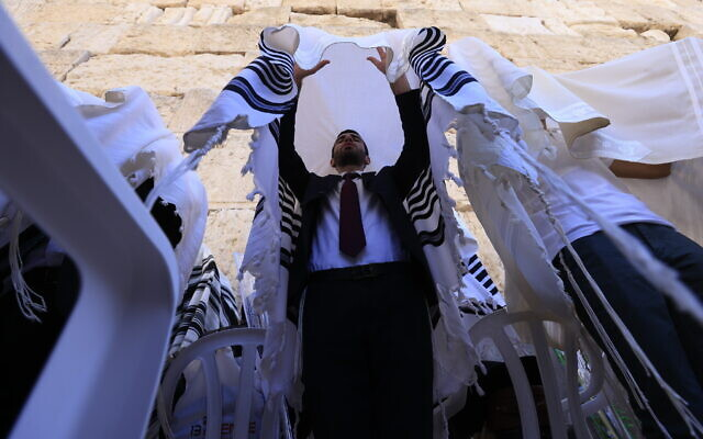 Worshippers pray in front of the Western Wall in Jerusalem's Old City, during the priestly blessing for the festival of Sukkot, on September 22, 2021. (Olivier Fitoussil/Flash90)
