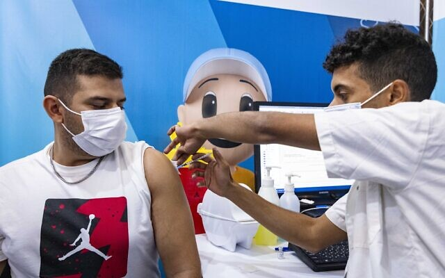 An Israeli receives a dose of the COVID-19 vaccine in Jerusalem, September 26, 2021 (Olivier Fitoussi/Flash90)