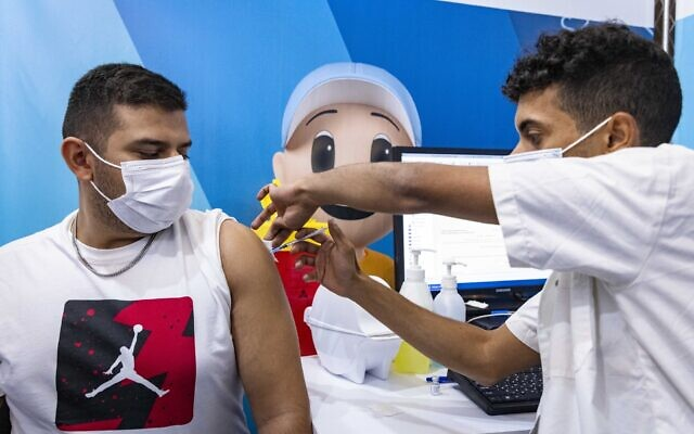 An Israeli receives a dose of the COVID-19 vaccine at a temporary Clalit Health Services facility in Jerusalem, September 26, 2021. (Olivier Fitoussi/Flash90)