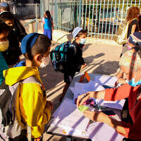 Young Israeli students have their antigen test results checked as they arrive for their first day of school after the holidays, at Aseh Hayil school in the West Bank settlement of Efrat, September 30, 2021 (Gershon Elinson/Flash90)