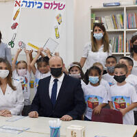 Prime Minister Naftali Bennett and Education Minister Dr. Yifat Shasha-Biton sit with children at the Eli Cohen Meuhad School in Yeruham, at the start of the new school year, on September 1 , 2021. (Haim Zach / GPO)