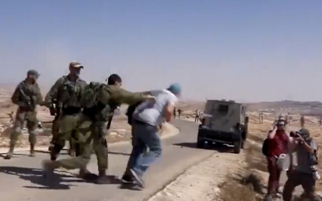 Video shows an Israeli soldier shoving an activist from the left-wing Combatants for Peace group during a protest in the southern West Bank, on September 17, 2021. (Screenshot/Twitter)