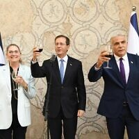 President Isaac Herzog (center), his wife, Michal, and Foreign Minister Yair Lapid, hold a toast ahead of the Jewish New Year for diplomatic corps, on September 2, 2021 in Jerusalem. (Amos Ben Gershom/GPO)