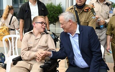 Defense Minister Benny Gantz, right, shakes hands with an IDF soldier during an event for the Sukkot holiday at the military's Kirya headquarters in Tel Aviv on September 23, 2021. (Tal Oz/Defense Ministry)