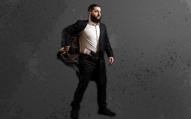 Rabbi Raziel Cohen demonstrates how to use the Tactical Kapota, a jacket designed for easily accessing a weapon. (Rabbi Raziel Cohen via JTA)
