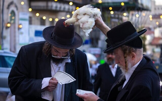 Ultra Orthodox Jews perform the Kapparot ceremony on September 13, 2021, in the Jerusalem neighborhood of Mea Shearim. (Olivier Fitoussi/Flash90)