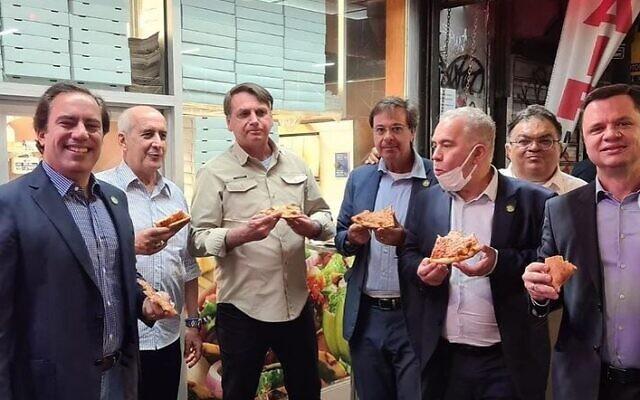 Brazilian President Jair Bolsonaro, center left, eats pizza on a New York sidewalk in a photo uploaded to social media on September 20, 2021. (Tourism Minister Gilson Machado/Instagram)
