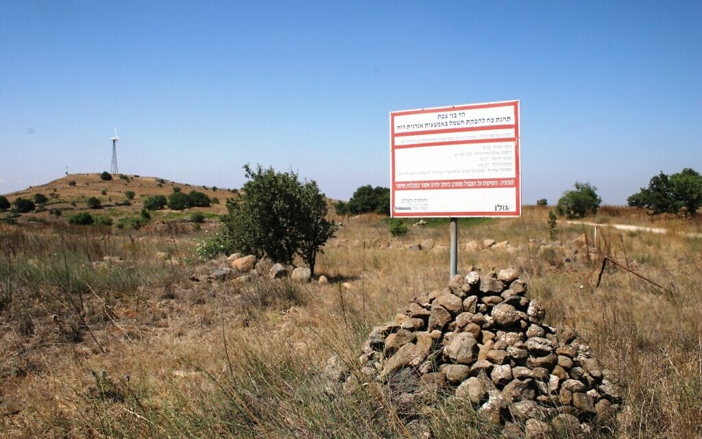 A sign explaining the energy contribution of the wind turbine dedicated to Simha Zeira in the Golan Heights, with the turbine memorial in the background. (Shmuel Bar-Am)